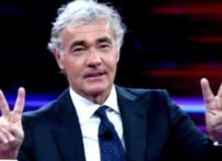 Massimo Giletti in giacca e cravatta fa il segno della pace