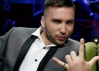 Mattia Briga in abito da sera grigio fa il gesto delle corna