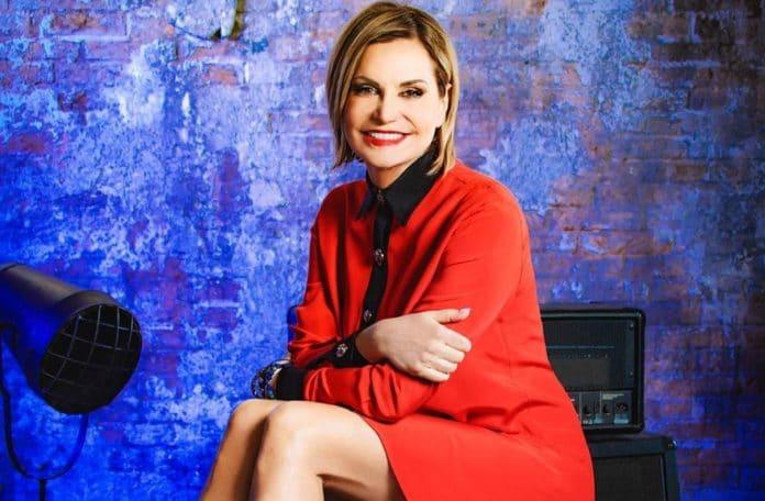 Simona Ventura in abito rosso sorride alla telecamera