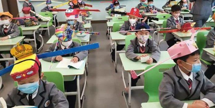 Bimbi cinesi che indossano il cappello della distanza